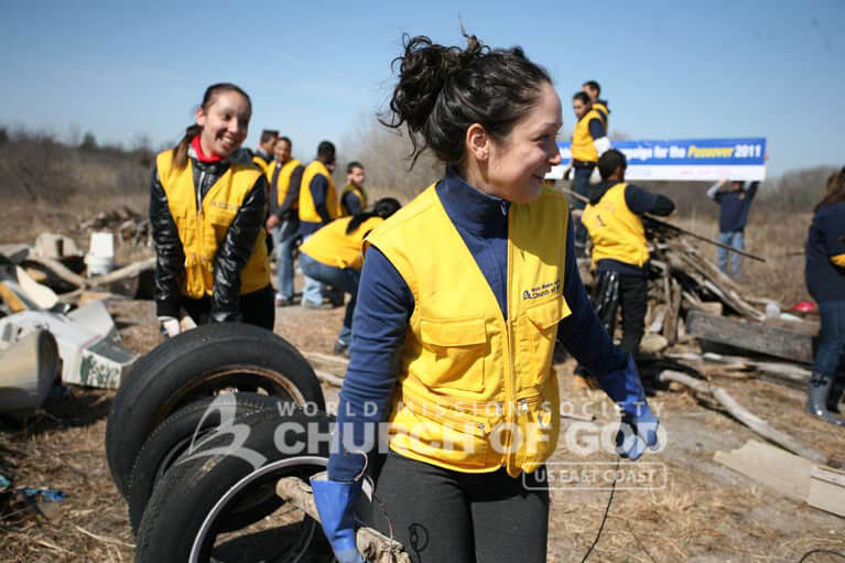Two World Mission Society Church of God volunteers moving old tires at Breezy Point Beach cleanup