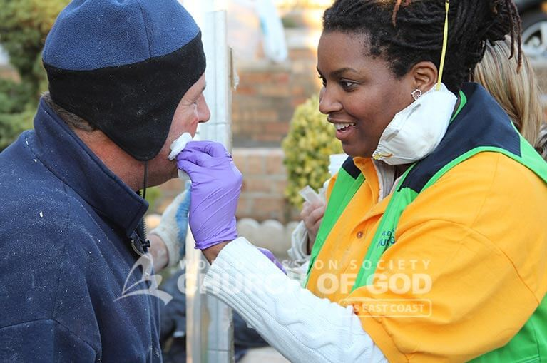 World Mission Society Church of God volunteer helps a NYC firefighter during Hurricane Sandy Relief Efforts