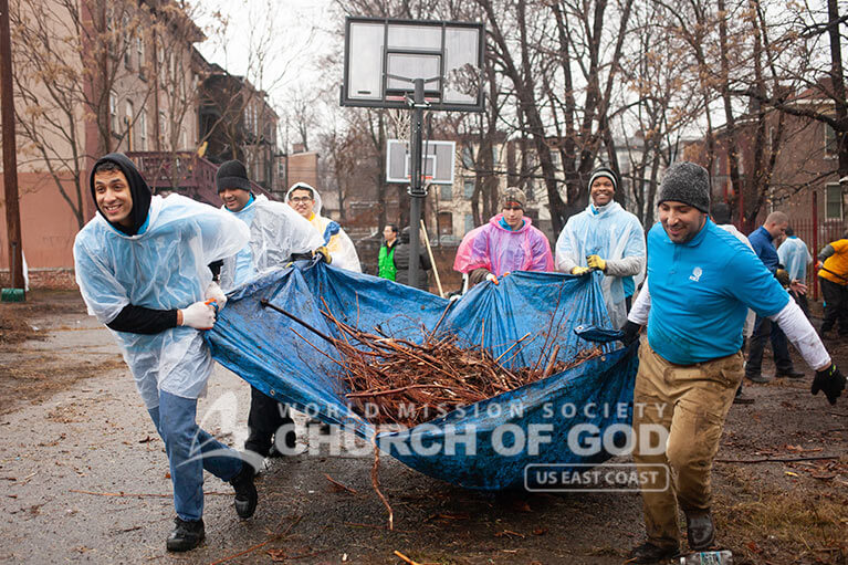 ASEZ volunteers from the World Mission Society Church of God holding a tarp of fallen branches during Mothers Street cleanup in Newburgh NY
