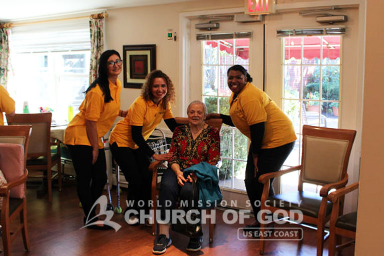World Mission Society Church of God volunteers posing with resident of Laurel Place Assisted Living during senior center visit