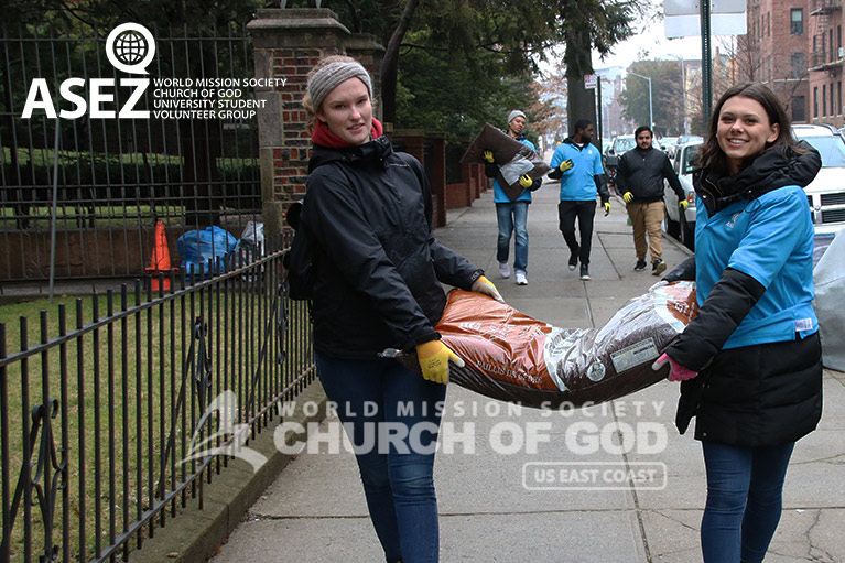 Two ASEZ volunteers from the World Mission Society Church of God carrying a bag of soil during Tree Stewardship at Brooklyn College