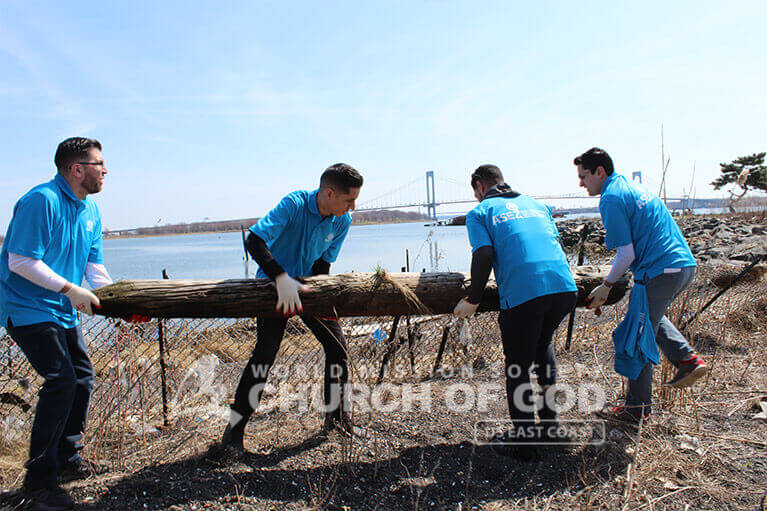 ASEZ volunteers carrying off a decaying log at Clason Point Park.