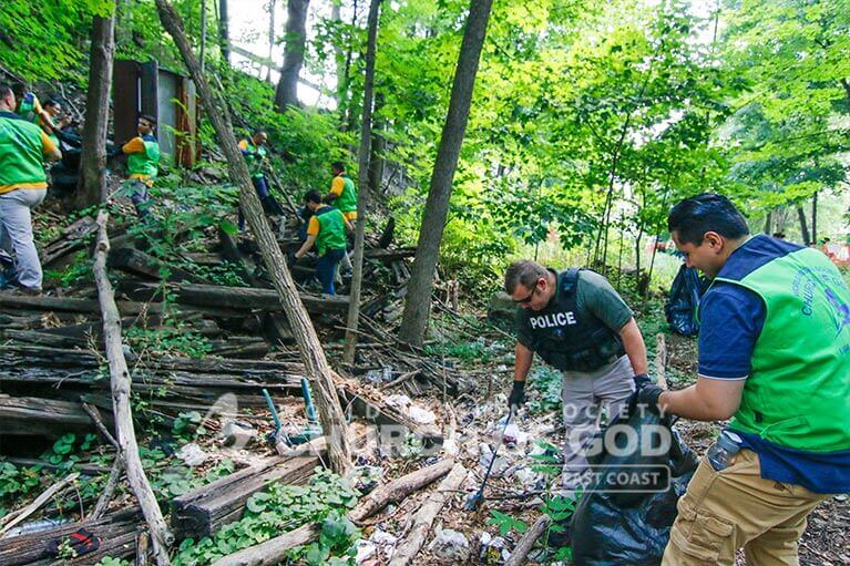 ASEZ WAO volunteer picking up trash with Middletown police officer at the Heritage Trail.