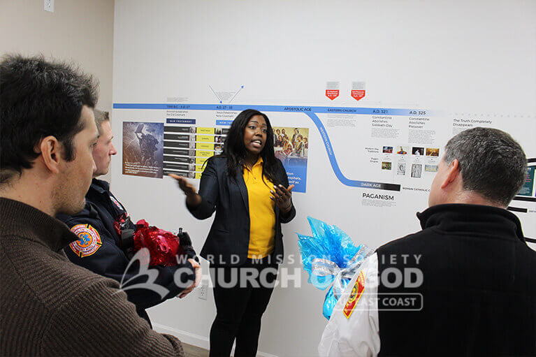 Church of God member giving the Westborough police officers a tour of the Christian history timeline