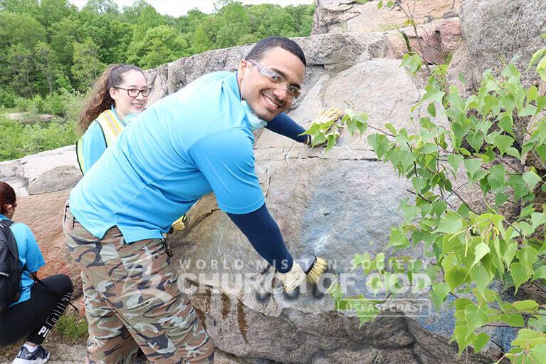 ASEZ volunteer happily removing graffiti at the Cranberry Lake Preserve