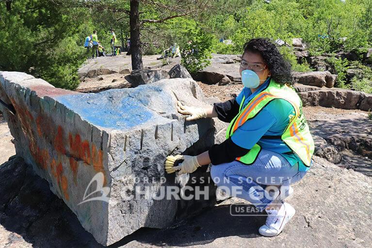 ASEZ student volunteer removing graffiti at the Cranberry Lake Preserve