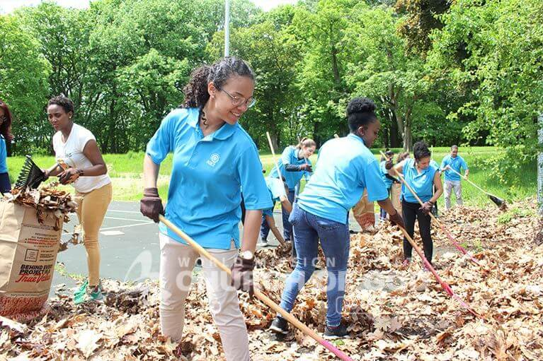 ASEZ volunteers removing dead leaves from tennis courts at Prospect Park in Troy, NY