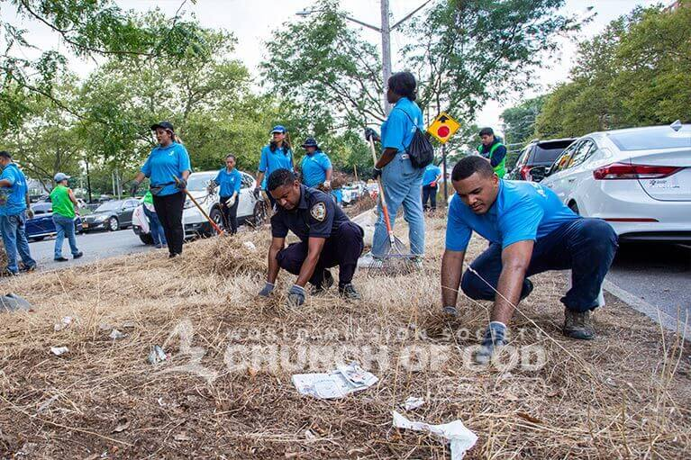 ASEZ volunteers and NYPD officer removing weeds from roadside