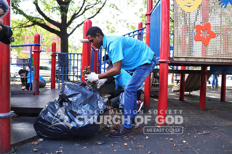 ASEZ student volunteers removing trash from a playground in Yonkers, NY