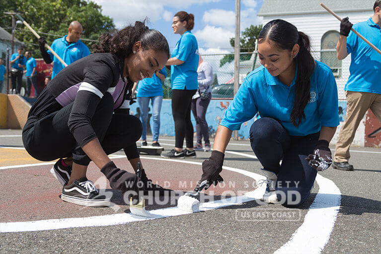 ASEZ student volunteers repainting the lines of a basketball court in Wrigley Park.