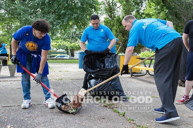ASEZ volunteers sweeping the park grounds at Wrigley Park.