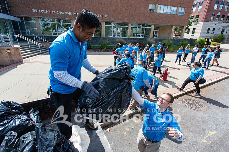 Volunteers from ASEZ moving trash bags off the street into a truck in Albany.