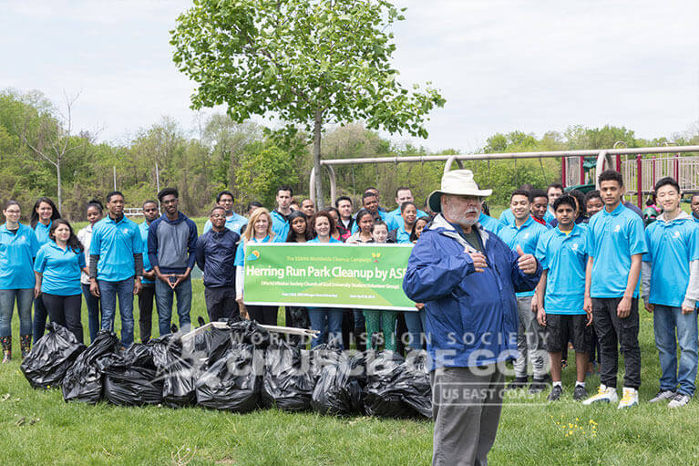 Parks and Recreation official speaking on the good deeds of ASEZ student volunteers after the Herring Run Park cleanup.