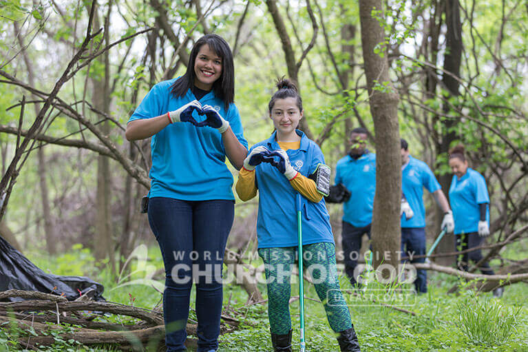ASEZ volunteers making hearts with their hands as they clean up Herring Run Park with love.