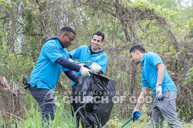 Volunteers from ASEZ joyfully cleaning up Herring Run Park.