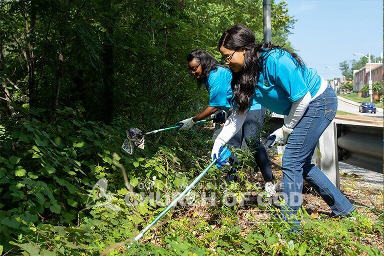 Volunteers from ASEZ removing trash from bushes along Mt. Pleasant Park.