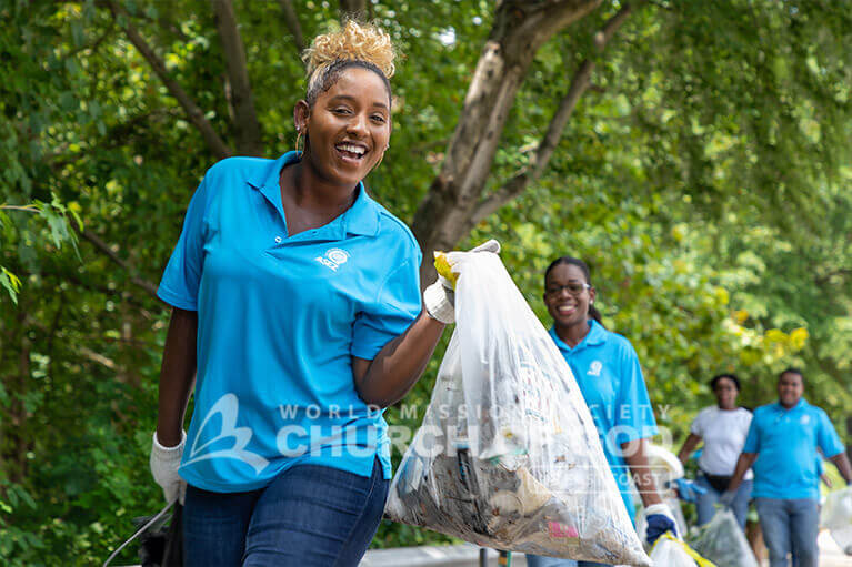 ASEZ volunteer smiling during the Mt. Pleasant Park cleanup in Baltimore, MD.