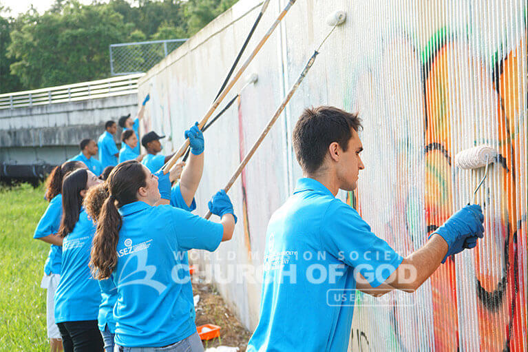 ASEZ volunteers removing graffiti from wall in Orlando.